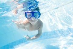 Niño que nada bajo el agua en piscina Fotos de archivo libres de regalías