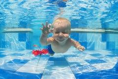 Niño que nada bajo el agua para una flor roja en la piscina Foto de archivo