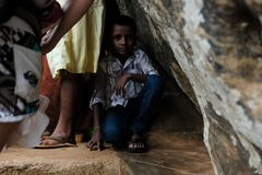 Niño que oculta de la lluvia tropical foto de archivo