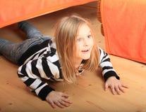 Niño que oculta debajo de cama Fotografía de archivo