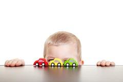 Niño que oculta detrás de los coches del juguete Fotos de archivo