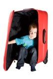 Niño que oculta en maleta y que mira a escondidas hacia fuera Imagen de archivo