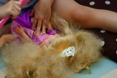Niño que peina el pelo de la muñeca de la princesa imagen de archivo libre de regalías