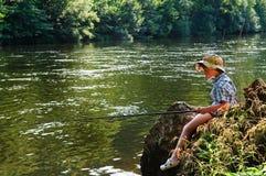 Niño que pesca con caña por el río Imagen de archivo