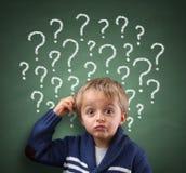Niño que piensa con el signo de interrogación en la pizarra Foto de archivo libre de regalías