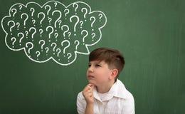 Niño que piensa con una burbuja del pensamiento de los signos de interrogación Imagen de archivo