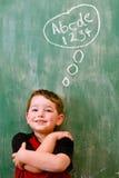 Niño que piensa en la escritura y la matemáticas Imagen de archivo
