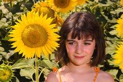 Niño que piensa en un campo del girasol Fotografía de archivo