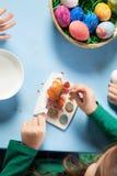 Niño que pinta los huevos de Pascua Foto de archivo