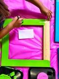 Niño que pinta un marco Foto de archivo
