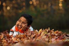 Niño que pone en las hojas del otoño Fotos de archivo
