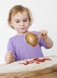 Niño que pone los tomates tamizados en la pasta imagen de archivo