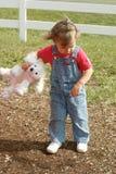 Niño que pone mala cara con el animal relleno a disposición Imagen de archivo