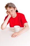 Niño que pone mala cara detrás de la taza blanca Imágenes de archivo libres de regalías