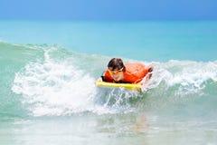 Niño que practica surf en la playa tropical Persona que practica surf en el océano Fotos de archivo
