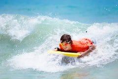 Niño que practica surf en la playa tropical Persona que practica surf en el océano Fotografía de archivo libre de regalías
