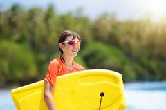 Niño que practica surf en la playa tropical Persona que practica surf en el océano Imágenes de archivo libres de regalías