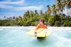 Niño que practica surf en la playa tropical Persona que practica surf en el océano Foto de archivo