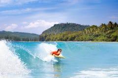 Niño que practica surf en la playa tropical Persona que practica surf en el océano Imagen de archivo