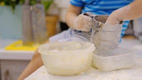 Niño que prepara la pasta en la tabla y los estornudos Pequeño bebé que juega con la harina El panadero prepara la pasta almacen de video