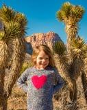 Niño que presenta en el barranco rojo de la roca, nanovoltio fotografía de archivo libre de regalías