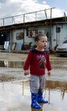 Niño que presenta en un charco con sus nuevas botas Imagenes de archivo