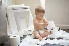 Niño que rasga para arriba el papel higiénico en cuarto de baño Imagen de archivo libre de regalías