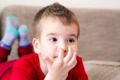 Niño que rasguña un finger en su nariz fotografía de archivo libre de regalías