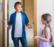 Niño que recibe el interior previsto del amigo en casa Imagen de archivo