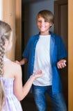 Niño que recibe el interior previsto del amigo en casa Imagenes de archivo