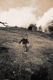 Niño que recorre abajo de la colina Fotos de archivo