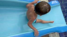 Niño que rueda abajo la diapositiva en piscina almacen de metraje de vídeo