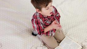 Niño que ruega en casa, Sagrada Biblia de la lectura del niño pequeño, niño cristiano en rodillas y llamando a dios almacen de video
