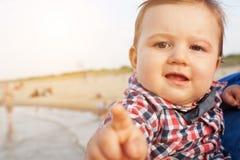 Niño que señala en la cámara con la expresión divertida en la playa Fotos de archivo libres de regalías