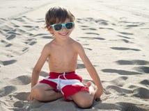 Niño que se arrodilla en la arena en la playa Fotos de archivo