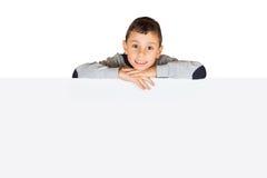 Niño que se coloca detrás de una bandera en blanco Fotos de archivo libres de regalías