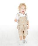 Niño que se coloca en el suelo blanco Imagen de archivo libre de regalías