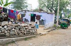 Niño que se coloca en la yarda de la casa asiática pobre de la familia Foto de archivo libre de regalías