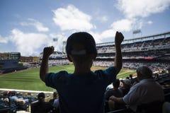Niño que se coloca y que anima en un juego de béisbol Imágenes de archivo libres de regalías