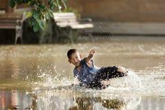 Niño que se desliza en cuadrado inundado Imagen de archivo