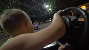 Niño que se divierte con la conducción del coche de parachoques en la feria de diversión almacen de video