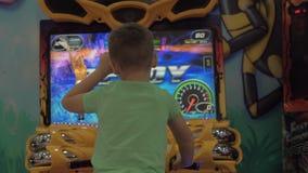 Niño que se divierte con la moto que compite con el simulador almacen de metraje de vídeo