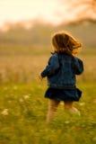 Niño que se ejecuta en campo en la puesta del sol Fotos de archivo libres de regalías
