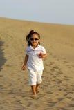 Niño que se ejecuta en desierto Imagen de archivo
