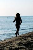 Niño que se ejecuta a lo largo de la playa Imagen de archivo