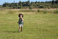 Niño que se ejecuta a través de campo Imagen de archivo