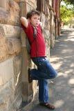 Niño que se inclina contra la pared Fotografía de archivo