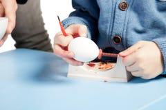 Niño que se prepara para pintar los huevos de Pascua fotografía de archivo libre de regalías