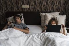 Niño que se relaja con el teléfono elegante y una tableta digital Imagen de archivo libre de regalías