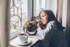 Niño que se relaja con un gato en un travesaño de la ventana Fotos de archivo